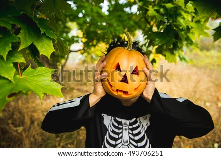 Portrait of a man in a suit holding a Halloween orange pumpkin. Skeleton. Studio in the woods