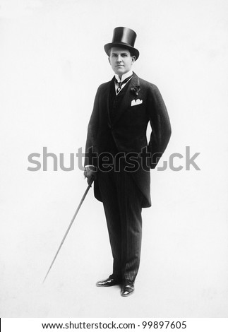 Portrait of a man in a top hat and morning suit holding a cane - stock photo