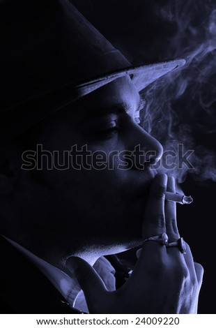 portrait of a man in black and white immensely enjoying the last puff from his cigarette in the light of the night - stock photo
