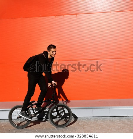 Portrait of a Man in black sportswear on a bicycle on a red wall in the sunny day smiling lifestyle