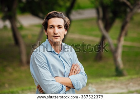 portrait of a man in blue shirt standing outside in park - stock photo