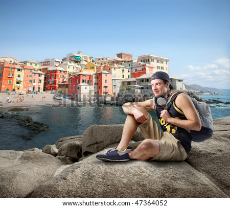 Portrait of a man in casual clothes sitting on a rock looking over a seascape and a typical village of the northern Italy coast - stock photo