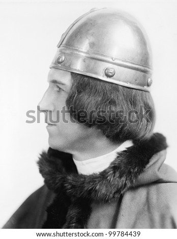Portrait of a man in costume and a helmet looking away - stock photo