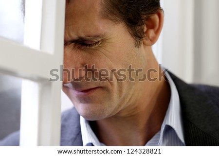 Portrait of a man in despair, misery or sorrow leaning against a window - stock photo