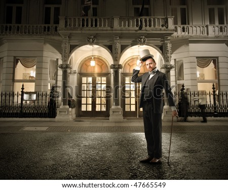 Portrait of a man in elegant suit standing in front of a palace - stock photo