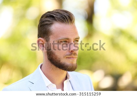 Portrait of a man in his 20s wearing a light blue blazer and white shirt, standing against a green background on sunny summer day.  - stock photo