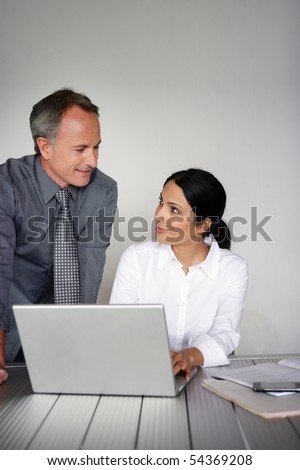 Portrait of a man in suit and a woman in front of a laptop computer - stock photo