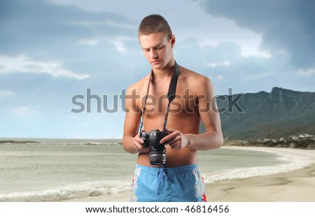 Portrait of a man in swimsuit carrying a camera round his neck - stock photo