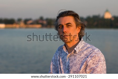 Portrait of a man in the background of the urban landscape with a lake at sunset. - stock photo