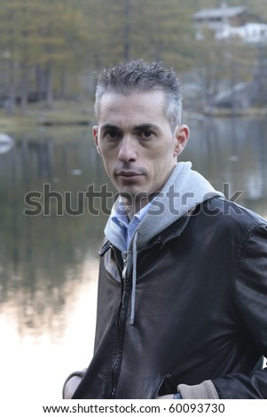 portrait of a man in the middle of nature in the background a mountain lake - stock photo