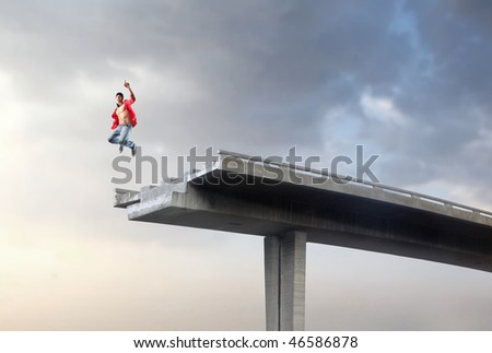 Portrait of a man jumping on a broken highway bridge