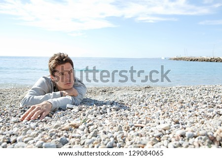Portrait of a man laying down on the shore of a white pebble beach being thoughtful with a blue sky and the sea in the background. - stock photo