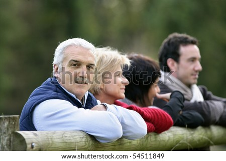 Portrait of a man leaning against a wooden fence - stock photo
