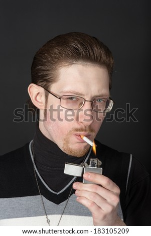portrait of a man lights a cigarette from lighter - stock photo