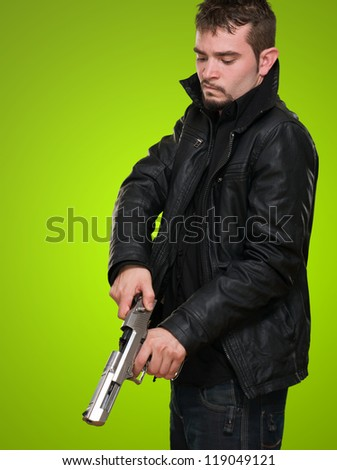 Portrait Of A Man Loading Gun against a green background