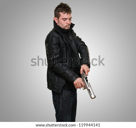 Portrait Of A Man Loading Gun against a grey background - stock photo