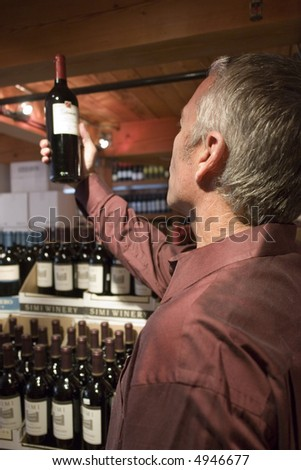 Portrait of a man looking at a wine bottle in a store - stock photo
