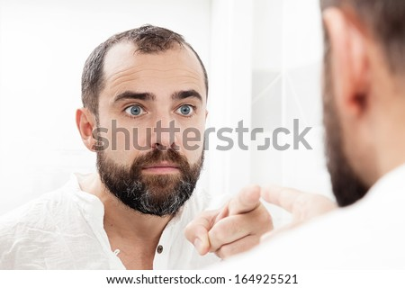 Portrait of a man looking in the mirror - stock photo