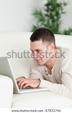 Portrait of a man lying on a sofa using a laptop in his living room