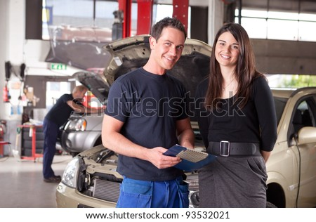 Portrait of a man mechanic with a woman customer going over the auto repair service report - stock photo