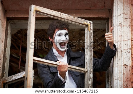 Portrait of a Man ??mime. Joyfully shouts, throwing an old wooden box - stock photo