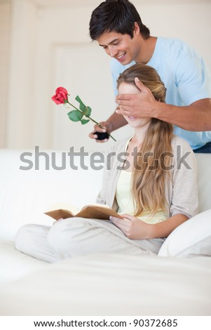 Portrait of a man offering a rose to his girlfriend while she is reading