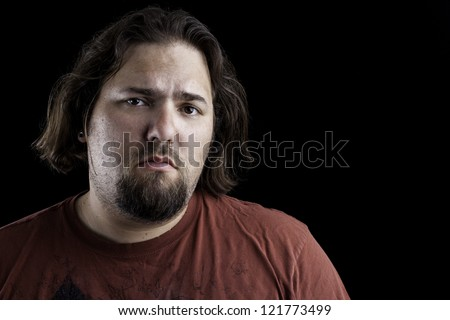 portrait of a man on black background with an expression that could be used as sad or depressed - stock photo