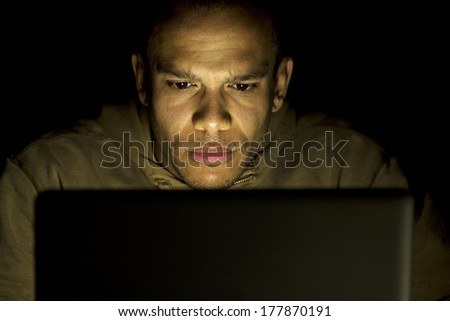 Portrait of a man on his laptop at night with a face of concentration. - stock photo