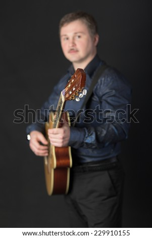 Portrait of a man playing a guitar (focus on the fretboard)