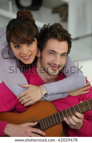 Portrait of a man playing guitar to his friend - stock photo