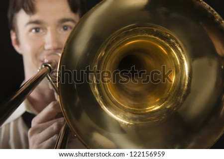 Portrait of a man playing trombone isolated over black background - stock photo
