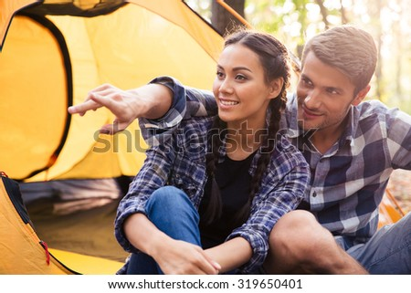 Portrait of a man pointing on something to his girlfriend in the forest  - stock photo