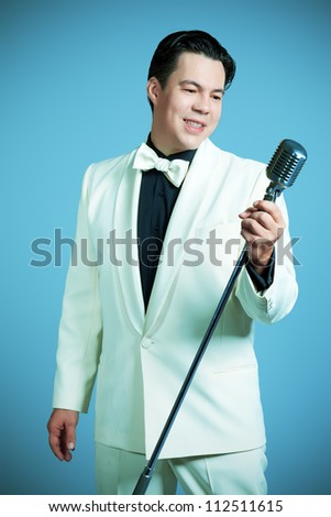 Portrait of a man professional singer in retro style posing in costume at studio. - stock photo