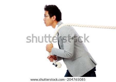 Portrait of a man pulling rope over white background - stock photo