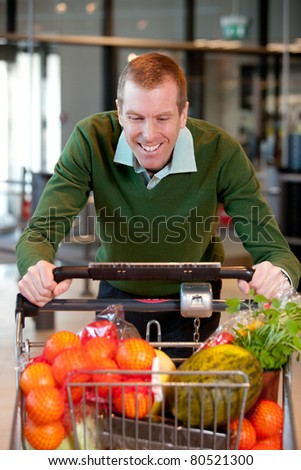 Portrait of a man pushing a grocery cart in a grocery store - stock photo