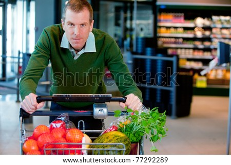 Portrait of a man pushing a grocery cart in a supermarket - stock photo