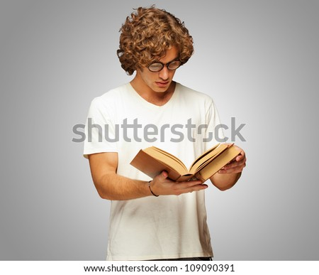 Portrait Of A Man Reading A Book Isolated On Grey Background