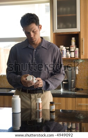 Portrait of a man reading a pill bottle - stock photo