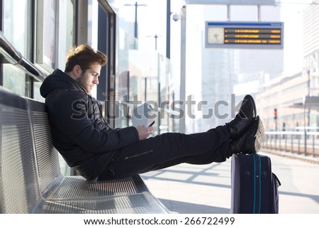 Portrait of a man relaxing by train station platform with bag and mobile phone - stock photo