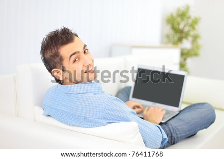 Portrait of a man relaxing on couch while using a laptop - stock photo