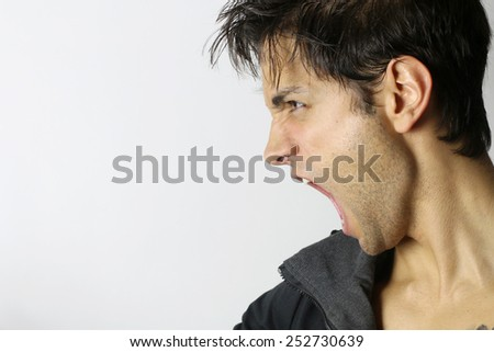 portrait of a man screaming in rage - stock photo