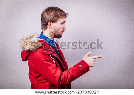Portrait of a man showing his finger to the side - stock photo