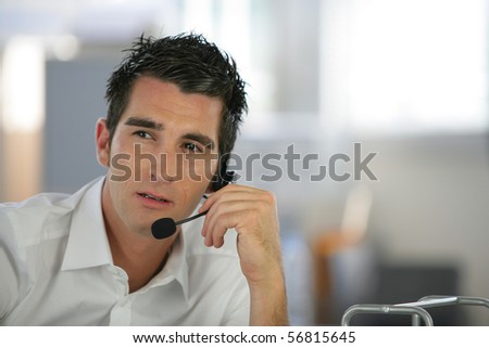 Portrait of a man sitting at a desk with a headset