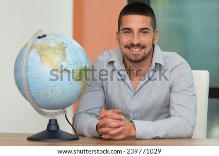 Portrait Of A Man Sitting By His Desk And Holding A Globe Model - stock photo