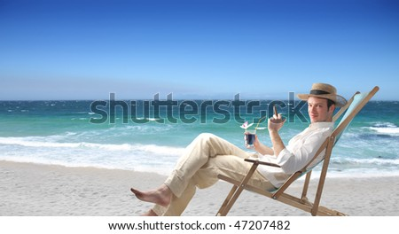 Portrait of a man sitting on a deckchair on a beach and holding a glass of wine and a cuban cigar - stock photo