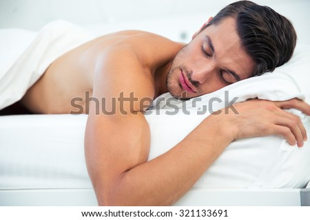 Portrait of a man sleeping in the bed at home - stock photo
