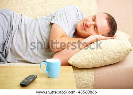 Portrait of a man sleeping on sofa in home with pillow under head. Blue cup and TV controller in foreground.