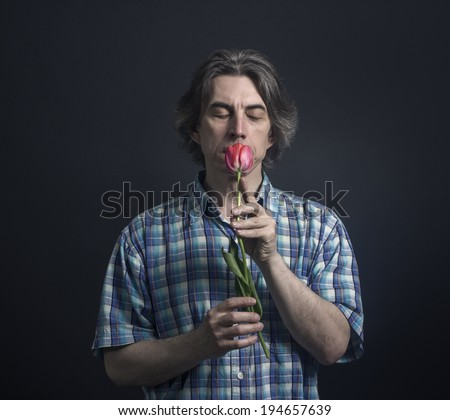 Portrait of a man sniffing tulip on a black background. - stock photo