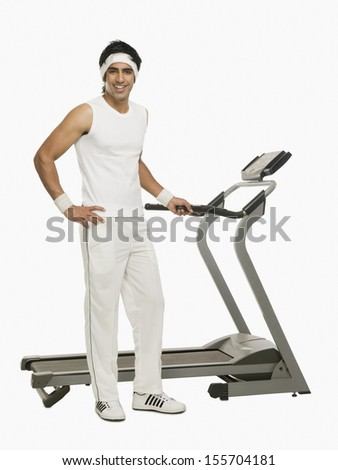 Portrait of a man standing beside a treadmill - stock photo