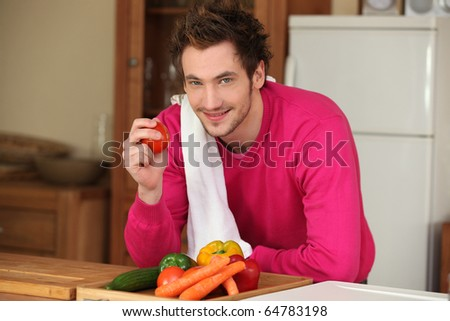Portrait of a man standing in the kitchen - stock photo